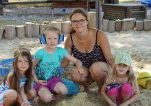 Junge Frau mit Kindern am Sandkasten