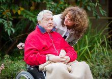 Junge Freiwillige neben einem alten Menschen im Rollstuhl