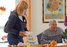Marion Sczepek mit Handtüchern, am Tisch eine lachende Bewohnerin