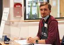 Sven Legens am Eingang, hinter einer offenen Plexiglasscheibe