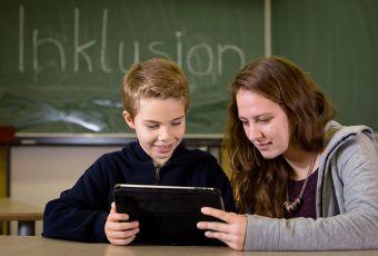 Inklusionshelferin mit jungem Schüler an einem Tablet-PC