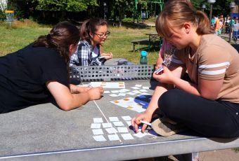 Drei Frauen legen kleine Karteikarten auf einer Tischtennisplatte aus