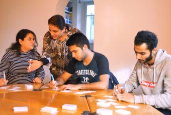 Flüchtlinge schreiben Stichworte auf kleine Karten