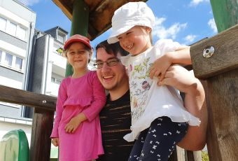 Junger Mann mit zwei Kindern auf den Schultern