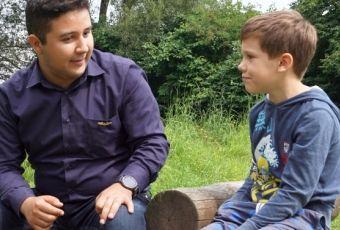 Freiwilliger im Gespräch mit Kind