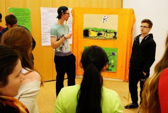 Zwei junge Männer stellen vor der Gruppe ihr Bild vor