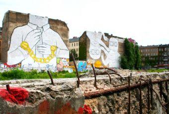Bemalte Betonbauten, auf einem großen Bild ein Mann in Handschellen