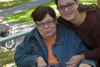 Junge Frau betreut Frau, die im Rollstuhl sitzt