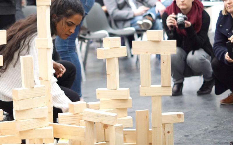 Jugendliche mit Holzbausteinen, auf denen Wünsche steheh